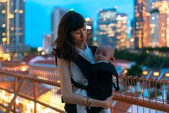 Young asian chinese mother traveling the city alone with baby in tow.  stock image