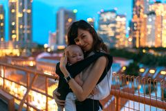 Young asian chinese mother traveling the city alone with baby in tow.  royalty free stock photography