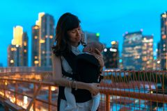 Young asian chinese mother traveling the city alone with baby in tow, showing her wedding ring. Young asian chinese mother traveling the city alone with baby in stock images