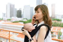 Young asian chinese mother traveling the city alone with baby in tow while working on the go.  royalty free stock photography
