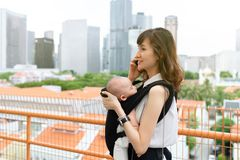 Young asian chinese mother traveling the city alone with baby in tow while working on the go.  stock image