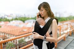 Young asian chinese mother traveling the city alone with baby in tow while working on the go.  stock images