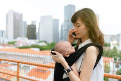 Young asian chinese mother traveling the city alone with baby in tow while working on the go.  stock photos