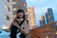 Young asian chinese mother traveling the city alone with baby in tow while working on the go.  royalty free stock image
