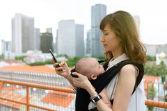 Young asian chinese mother traveling the city alone with baby in tow while working on the go.  stock photo