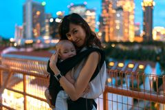 Young asian chinese mother traveling the city alone with baby in tow.  stock images
