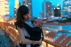 Young asian chinese mother traveling the city alone with baby in tow.  stock photography