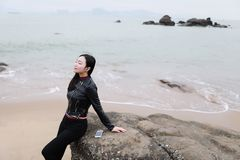 Young asian chinese woman Listen to the music sit on rock of Sand Beach royalty free stock photography