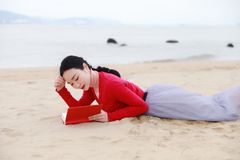 Young asian chinese woman read Lying on her side in the Sand Reading Book At Beach royalty free stock images