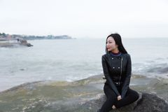 Young asian chinese woman sit on rock of sea , Listen to the voice of the sea. Long hair romantic woman relax sit on rock and Listen to the voice of the sea at stock images