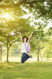 Young Asian college girl student open arms jumping Stock Photo