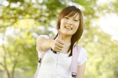 Young Asian college girl student thumb up Royalty Free Stock Images