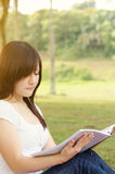 Young Asian college student reading book Royalty Free Stock Photography