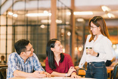 Young Asian college students or coworkers social meeting at coffee shop. Diverse group. Casual business, freelance work at cafe, or education concept Stock Photos