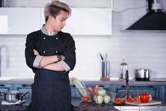 Asian cook in the kitchen prepares food in a cook suit stock photo