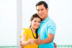 Young Asian couple in apartment with thumbs up Royalty Free Stock Photography