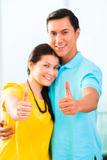 Young Asian couple in apartment with thumbs up Royalty Free Stock Images