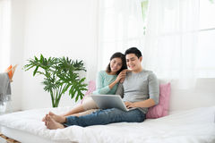 Young asian couple browsing internet at home,using laptop and sm Stock Photography