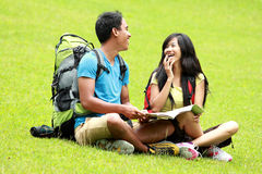 Young asian couple chatting and sitting on the grass. A portrait of a young asian couple chatting and sitting on the grass, map on the man's lap stock photos