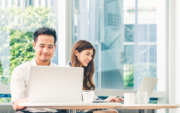 Young Asian couple or college student using laptop computer notebook work together at coffee shop or university campus royalty free stock photo