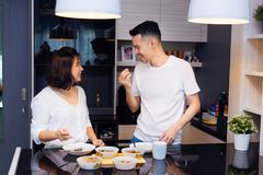 Young Asian couple cooking together while woman is feeding food to man at the kitchen. Happy couple and relationship concept. royalty free stock images