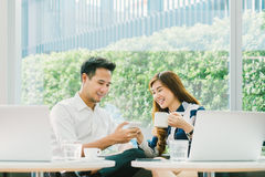 Young Asian couple, coworkers, or business partners have fun using smartphone together, with laptop computer at coffee shop royalty free stock images