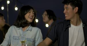 Young asian couple dancing and having fun celebrating New Year and Christmas Festival together at summer rooftop party.