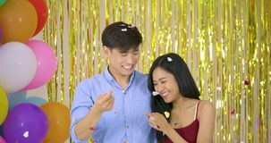 Young asian couple enjoy with confetti over gold glitter background. Young asian couple enjoy with confetti over gold glitter background, slow motion stock video footage