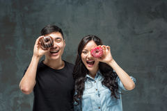 Young asian couple enjoy eating of sweet colorful donut royalty free stock image