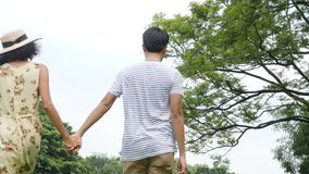 Young asian couple enjoying in spring day in nature and going on picnic with happy emotion. stock video footage