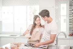 Young Asian couple happy loving couple bakers helping to make dinner. Young Asian couple happy loving couple bakers helping to make dinner Royalty Free Stock Images