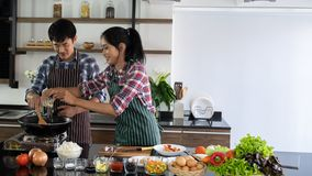 Young Asian couple are happy to cook together, And help to cook food in the morning royalty free stock image