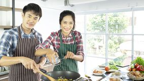 Young Asian couple are happy to cook together on holiday royalty free stock photography