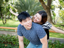 Young Asian couple having piggy back together in green nature ba Royalty Free Stock Images