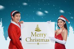 Young asian couple holding banner with Merry Christmas message Stock Photo
