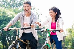 Young Asian couple laughing together while riding bicycles. Outdoors in summer Stock Images