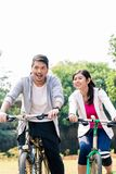 Young Asian couple laughing together while riding bicycles. Outdoors in summer Royalty Free Stock Photography