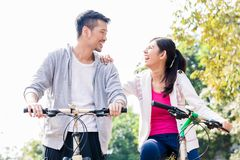 Young Asian couple laughing together while riding bicycles Royalty Free Stock Photos