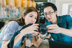 Young Asian couple learning to use mirrorless digital camera together at coffee shop royalty free stock image