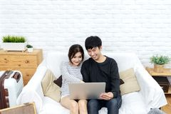 Young asian couple looking at laptop computer to search for travel plan, book hotel room, buy ticket or purchase travel insurance. Together at sofa in living royalty free stock image
