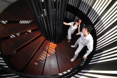 Young Asian Couple in Love climbing spiral stairs stock photos