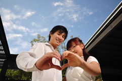 Young Asian Couple in Love forming a heart shape Royalty Free Stock Photography