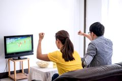 Young Asian couple love watching soccer match on tv and cheering. Football team, celebrating with beer and popcorn at home, sports and entertainment concept Stock Photos
