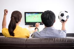 Young Asian couple love watching soccer match on tv and cheering. Football team, celebrating with beer and popcorn at home, sports and entertainment concept Royalty Free Stock Photo