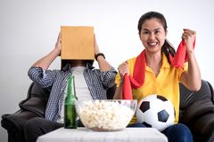 Young Asian couple love watching soccer match on tv and cheering. Football team, celebrating with beer and popcorn at home, sports and entertainment concept Stock Photography