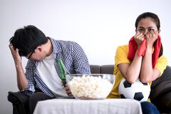 Young Asian couple love watching soccer match on tv and cheering. Football team, celebrating with beer and popcorn at home, sports and entertainment concept Royalty Free Stock Images