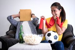 Young Asian couple love watching soccer match on tv and cheering. Football team, celebrating with beer and popcorn at home, sports and entertainment concept Stock Images