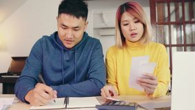 Young asian couple managing finances, reviewing their bank accounts using laptop computer and calculator at modern home. Woman and man doing paperwork together stock video footage