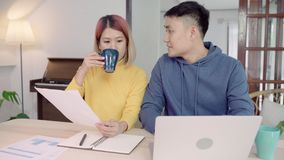 Young asian couple managing finances, reviewing their bank accounts using laptop computer and calculator at modern home. Woman and man doing paperwork together stock video
