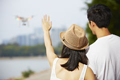 Young asian couple operating a drone Stock Photos